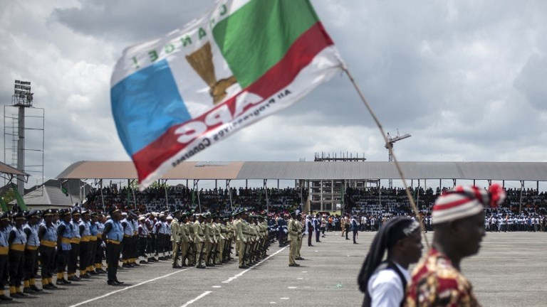 A man walks with an All Progressive Congress (APC) political party flag during a Democracy Day parade on May 29, 2017 in Freedom Square in Owerri. Democracy Day celebrates the end of military rules in Nigeria in May of 1999. / AFP PHOTO / STEFAN HEUNIS