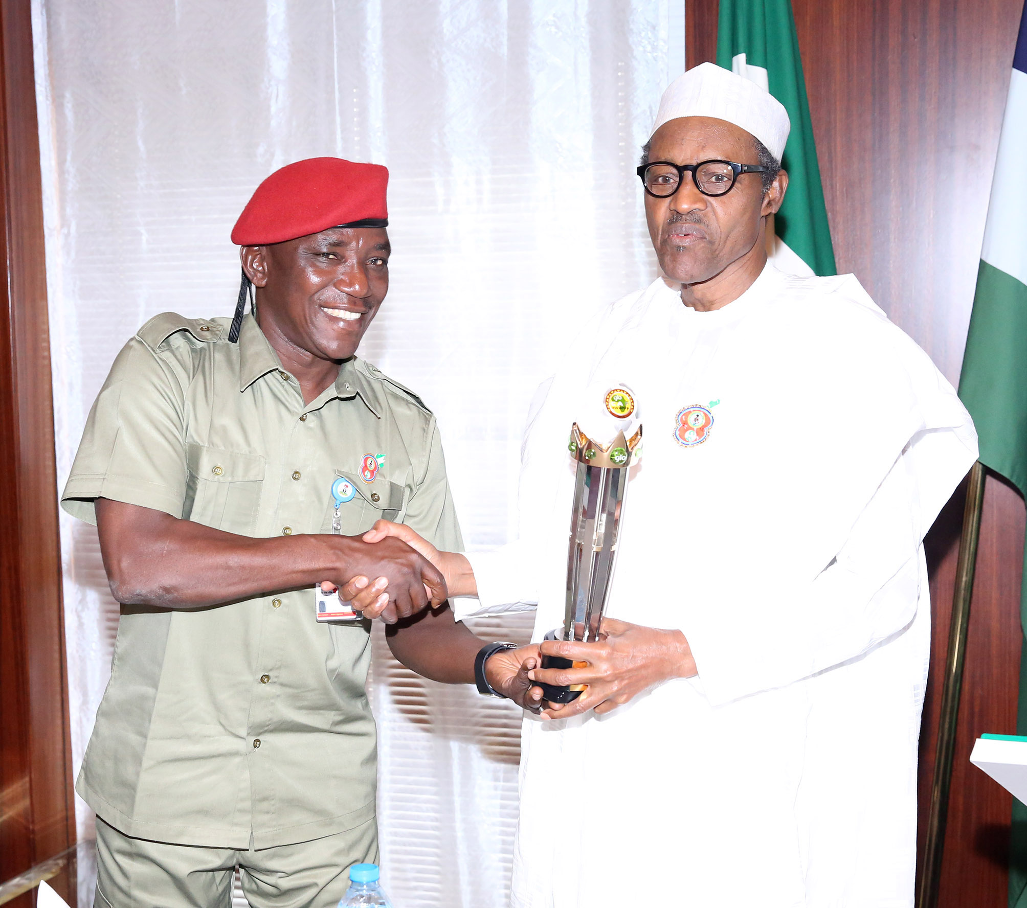 PRESIDENT BUHARI RECEIVES GLO CAF AWARD 1A&B. President Muhammadu Buhari being presented with the GLO CAF Platinum Award Trophy by the the Minister of Youth and Sports, Barrister Solomon Dalung for Good Leadership at the State House in Abuja. PHOTO; SUNDAY AGHAEZE. JAN 11 2016.