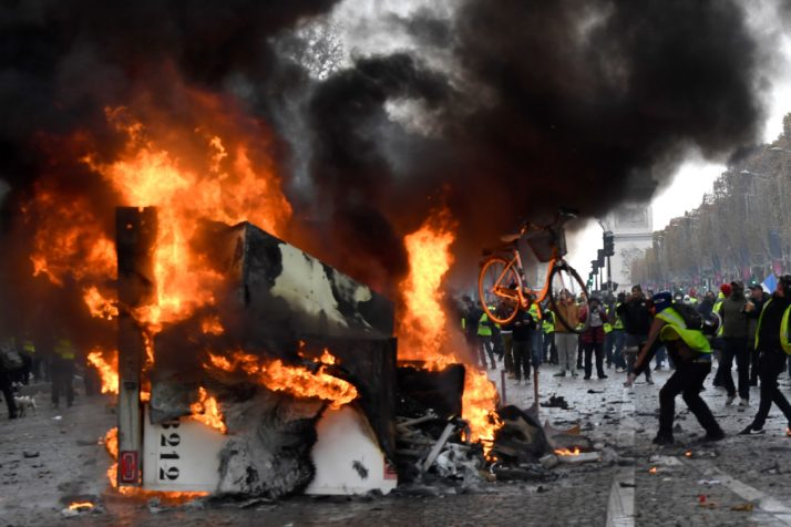 "A man throws a bike in a burning truck during a protest of Yellow vests (Gilets jaunes) against rising oil prices and living costs near the Arc of Triomphe on the Champs Elysees in Paris, on November 24, 2018. - Police fired tear gas and water cannon on November 24 in central Paris against ""yellow vest"" protesters demanding French President Emmanuel Macron roll back tax hikes on motor fuel. (Photo by Bertrand GUAY / AFP) (Photo credit should read BERTRAND GUAY/AFP/Getty Images)"