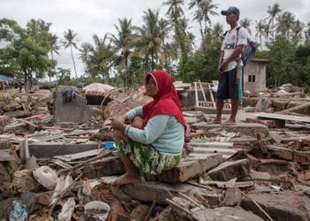 An Indonesian tsunami victim sits on the ruins of her house after a tsunami hit the Sunda Strait, in Paniis Village, Pandeglang, Banten, Indonesia on Dec. 25, 2018. Zulkifli, EPA-EF