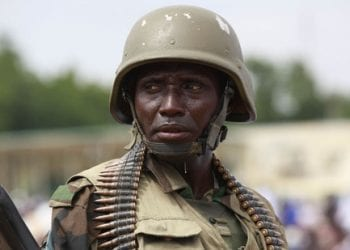In this photo taken Thursday, Aug. 8, 2013, a Nigerian soldier stand guards during Eid al-Fitr prayers in Maiduguri, Nigeria. Suspected Islamic militants wearing army fatigues gunned down 44 people praying at a mosque in northeast Nigeria, while another 12 civilians died in an apparently simultaneous attack, security agents said Monday Aug. 12, 2013. The slayings occurred Sunday morning at a mosque in Konduga town, some 35 kilometers (22 miles) outside Maiduguri, the capital of Nigeria's Borno state. (AP Photo/Sunday Alamba)