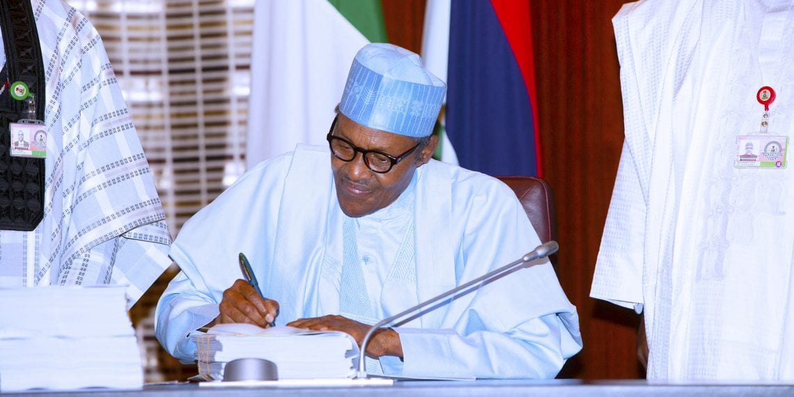 PRESIDENT BUHARI SIGN 2019 BUDGET 1A; President Muhammadu Buhari signs the 2019 Budget during the signing of the 2019 Budget. Others are Leadership of National Assembly and Cabinet members. PHOTO; SUNDAY AGHAEZE MAY 27 2019